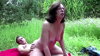 Horny old granny has outdoor sex with a young stud