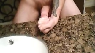 Tattooed guy masturbating and rubbing big dick to cum in sink
